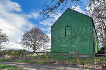 A rural farm shed painted in green at a farmland in British countryside of England, UK