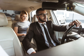 handsome driver and attractive businesswoman in car
