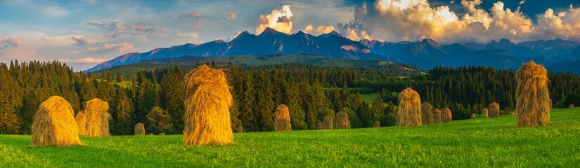 spring panorama of the Tatra Mountains in Poland during the sunset, stacks of hay after haymaking