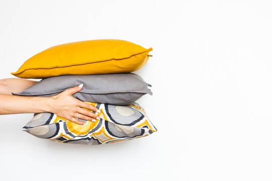 Colorful pillows in women's hands on a white isolated background, the concept of home comfort6 close up, copy space