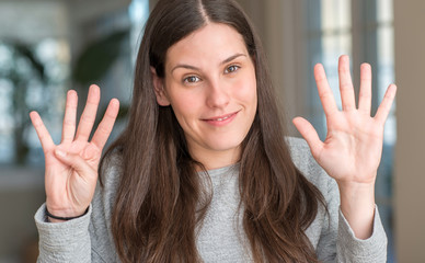Young beautiful woman at home showing and pointing up with fingers number nine while smiling confident and happy.