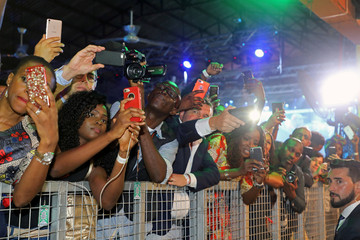 People take pictures of French President Emmanuel Macron as he arrives to take part of a live show at the Afrika Shrine in Lagos