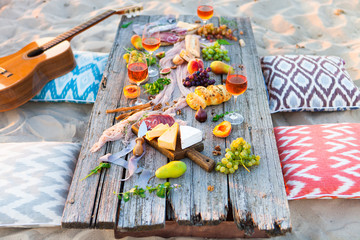 Aluminium Prints Picnic Picnic on beach at sunset in boho style. Romantic dinner, friends party, summertime, food and drink concept