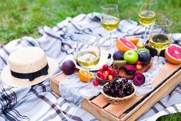 Aluminium Prints Picnic Picnic background with white wine and summer fruits on green grass, summertime party