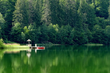 Mountain lake in the forest with a boat
