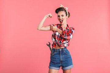 Gorgeous strong young pin-up woman showing biceps. Wall mural