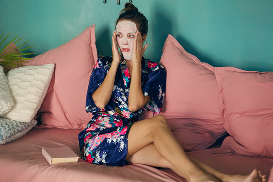 Beautiful young lady in a navy blue satin robe, sitting on the pink couch, enjoying her beauty procedures at home. The slim brunette woman applying a white face sheet mask, going to read a book.