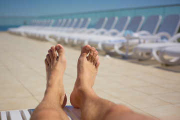 men's legs on the background of sun loungers by the pool. Travel, healthy lifestyle