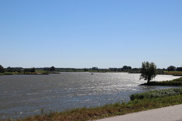 River lek, which is a lateral of river Rhine, with dykes in the sun in the Netherlands