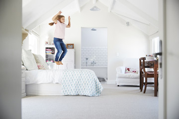 Happy young girl jumping on her bed in her bedroom