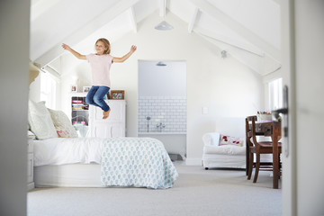 Happy young girl jumping on bed in her bedroom