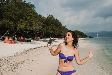 .Young woman on vacation in the gili islands enjoying at the lonely beach with turquoise blue water, relaxing, sunbathing and listen to music with her smartphone. Travel photography.