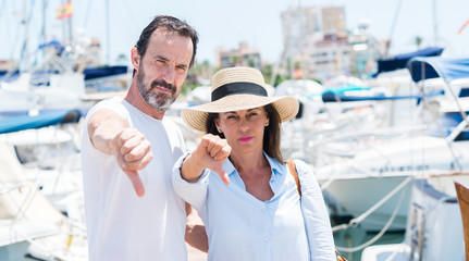 Middle age couple in marina with angry face, negative sign showing dislike with thumbs down, rejection concept