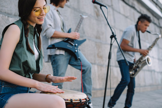 Happy woman and men with musical instruments performing on sunny city street