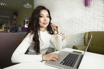 Positive attractive hipster girl with long hair chatting with friends and reading funny information. Student studying with laptop and taking notes on laptop.
