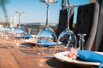 Romantic wedding or another catered event table setting, flowers, white plates, blue napkins, wine glasses, Event decoration, summer time, outdoors