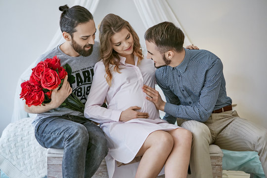 Gay couple becoming parents through surrogacy. 2 guys sitting on the bed, a pretty surrogate mom between them. One of the fathers-to-be holding roses, the other putting his hand on the pregnant belly.