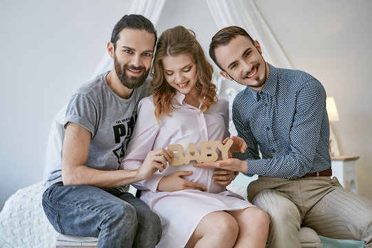 Gay couple becoming parents through surrogacy. The fathers-to-be sitting on the bed, a  surrogate mom between them, happy smiles on their faces. The men holding lettering BABY over the pregnant belly.