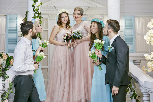 b42e3ee76d3 Two brides in light pink and bridesmaids in blue enjoying morning in the  hotel room. The happy newlyweds focusing on each other