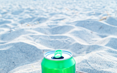 Green can on a beach to illustrate waste and mass tourism in tourist areas and beaches