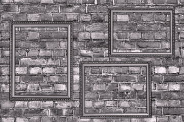 old grey brick wall with three frames