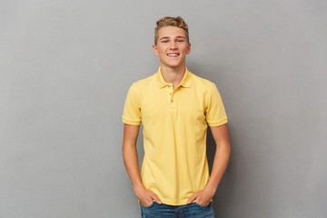 Portrait of a smiling casual teenage boy standing Wall mural