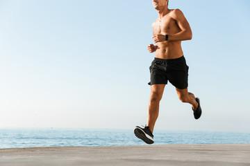 Cropped image of shirtless sportsman running