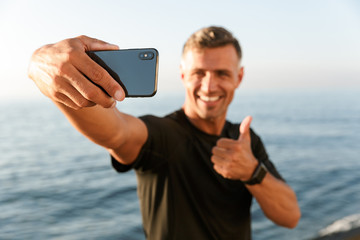 Smiling handsome shirtless sportsman taking a selfie