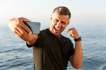 Cheerful handsome shirtless sportsman taking a selfie