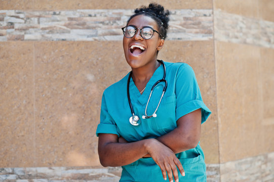 African american doctor female at lab coat with stethoscope posed outdoor against clinic.