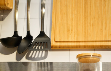 View of the kitchen counter with cutting Board, hanging on the wall a few useful devices. Shovel for frying pan. A ladle and a large spoon. Glass jar with cover for grain