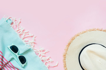 Straw beach sunhat and sun glasses on punchy pink with space for text. Female outfit for beach. Summer concept.