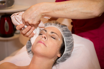 remove mask on woman face by professional esthetician in spa beauty center