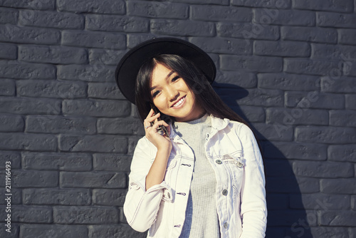 d4779c4be0366 Happy asian hipster girl looking at camera while standing against wall with  copy space for advertising. Beautiful young woman talking on mobile phone  near ...