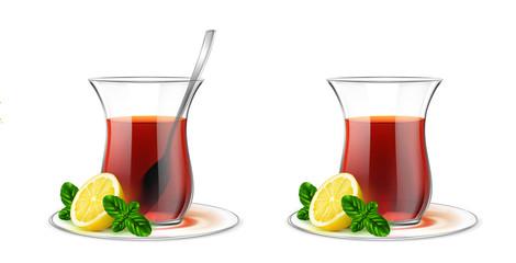 Turkish transparent tea cup with black tea, silver spoon, mint and lemon