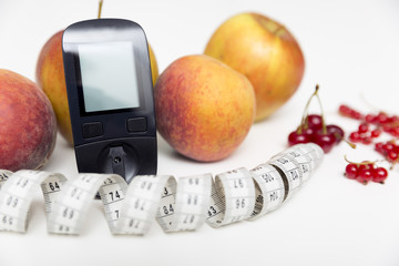 Diabetes monitor, diet and healthy food eating nutritional concept with clean fruits with diabetic measuring tool kit ans measuring tape