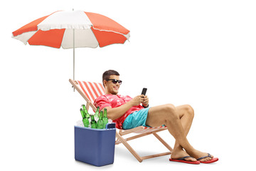 Tourist with a phone sitting in a deck chair with an umbrella next to a cooling box