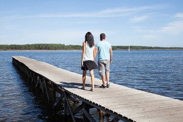 couple in love in vacation walk on pontoon lake beach sea