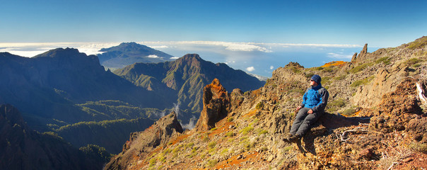 Photo sur Aluminium Bleu nuit Resting man watching a landscape above the crater Caldera de Taburiente, Island of La Palma, Canary Islands, Spain