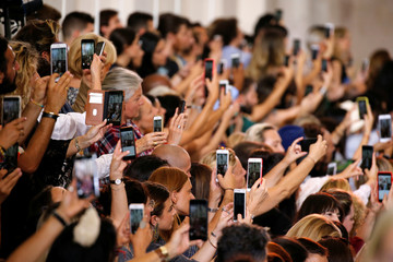Guests take pictures with their mobile phones as models present creations by designer Elie Saab as part of his Haute Couture Fall/Winter 2018/2019 fashion show in Paris