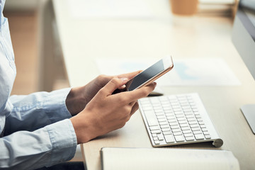 Crop side view of woman using smartphone while sitting at computer desk in daylight