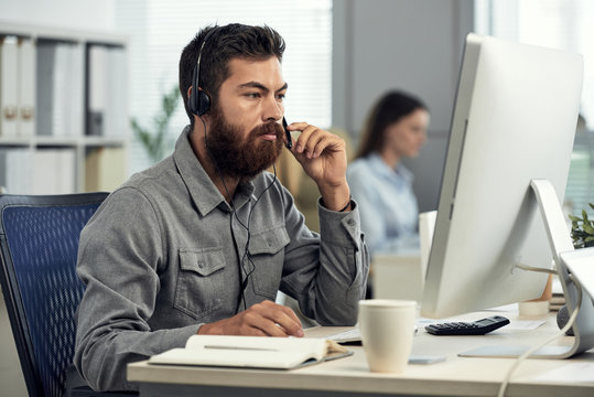 Brutal bearded man in shirt wearing headset and sitting at computer desk in call center