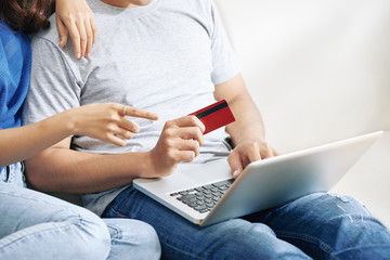 Faceless shot of couple buying via Internet while using laptop and credit card for shopping