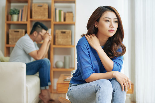 Sad Asian woman sitting alone with man on background being in conflict at home