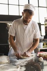 Male baker preparing dough in bakery shop