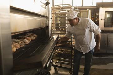 Male baker using baking owen in bakery shop