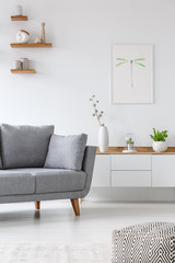 Real photo of a grey couch standing next to  shelf with vases in a white living room with a poster on a wall