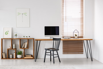 Real photo of a long table with a computer screen standing with a black chair next to a wooden shelf with ornaments and a wall with poster, and a window with blinds in a bright office interior