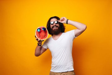 Half of Watermelon face with glasses held by a bearded man. Hipster wearing white shirt with long hair. Summer offer, vacation, holiday rest. Traveling and tourism concept. Summer buddy.  Wall mural