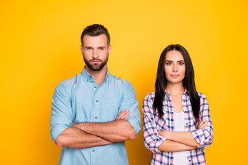 Portrait of confident stylish couple holding arms crossed looking at camera isolated on vivid yellow background Wall mural
